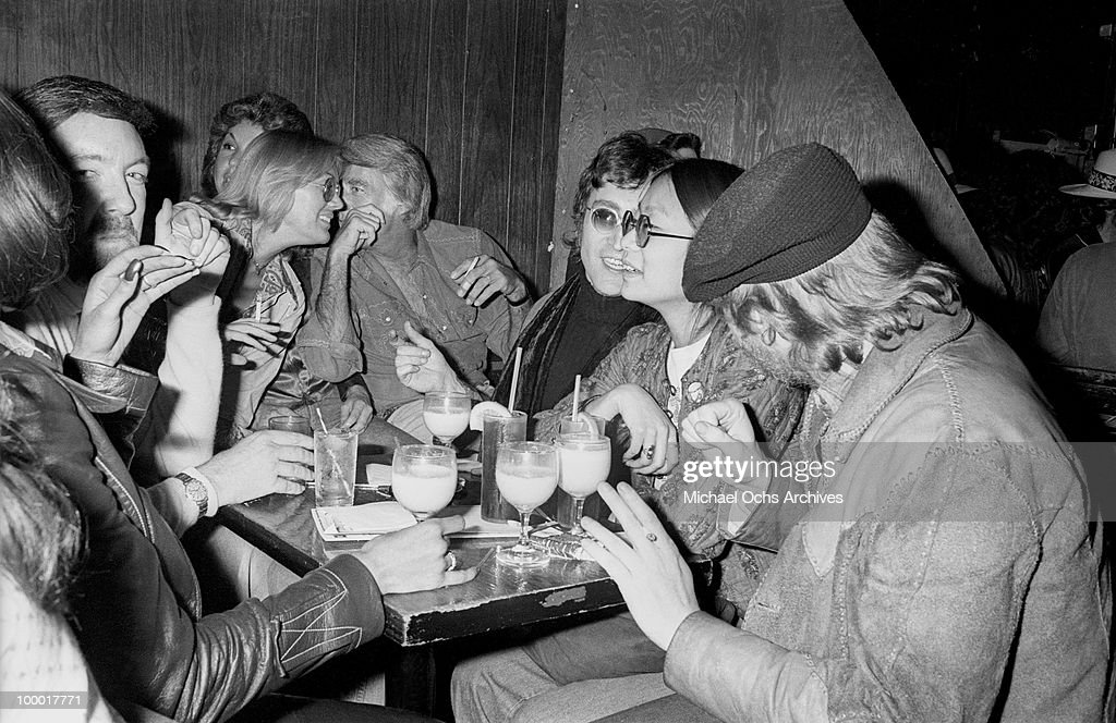 Singer-guitarist John Lennon, formerly of The Beatles, attends a Smothers Brothers comedy performance with girlfriend May Pang, Peter Lawford (center), Jack Haley Jr. (left) and singer-songwriter Harry Nilsson (right), during Lennon's infamous 'Lost Weekend' period, at the Troubadour on March 12, 1974, in West Hollywood, California. Lennon and Nilsson would later be kicked out of the show for drunken heckling.