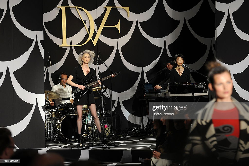 Singer/musician St. Vincent (L) and guitarist/mini moog player Toko Yasuda perform as a model walks the runway at the American Express UNSTAGED Fashion with DVF at Spring Studios on February 9, 2014 in New York City.