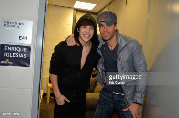 Singers Austin Mahone and Enrique Iglesias pose backstage at Hot 995's Jingle Ball 2013 presented by Overstockcom at Verizon Center on December 16...