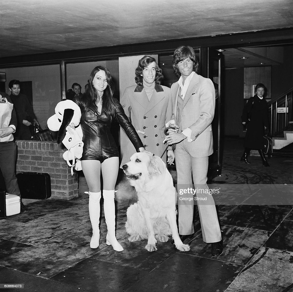 Singers Barry (right) and Robin Gibb (1949 - 2012) of the Bee Gees return from the US with Barry's wife, former Miss Edinburgh Linda Gray, London Airport, UK, 8th March 1971.