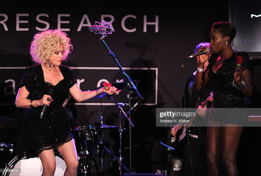 Singers Cyndi Lauper and Estelle perform onstage during the 2010 amfAR New York Inspiration Gala at The New York Public Library on June 3 2010 in New...