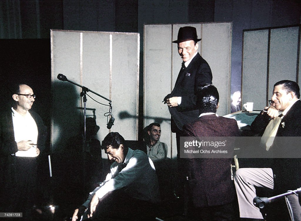 Singers Dean Martin (seated in white shirt), Sammy Davis, Jr. (seated next to Dean Martin) and Frank Sinatra (in hat) record in the studio in October 1962 in Los Angeles, California.