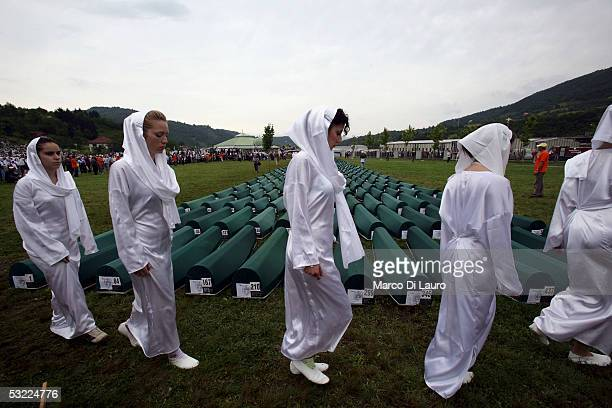 SREBRENICA BOSNIA HERZEGOVINA JULY 11 Singers from a choir walk past the 610 coffins of some of the Srebrenica massacre victims prior to the funeral...