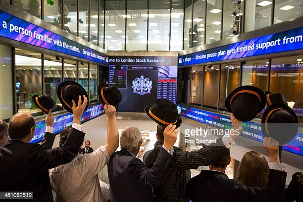 Singers from office choirs conducted by City of London Festival director Paul Gudgin raise bowler hats after opening the London Stock Exchange with a...
