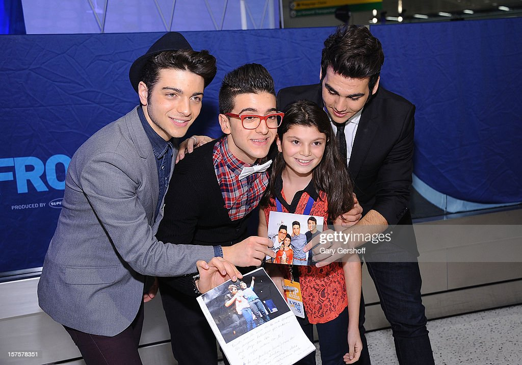 Singers Gianluca Ginoble, Piero Barone and Ignazio Boschetto of ll Volo pose for pictures with a fan prior to perfoming at jetBlue Terminal 5 at JFK Airport on December 4, 2012 in New York City.