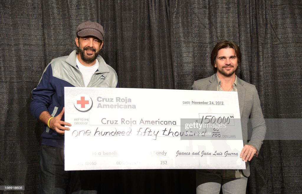 Singers Juan Luis Guerra (L) and Juanes and hold up a donation check to help victims of hurricane Sandy at Barclays Center of Brooklyn on November 24, 2012 in New York City.