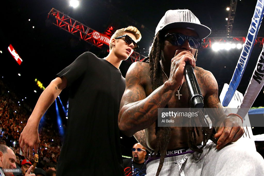 Singers Justin Bieber and Lil Wayne enter the ring with Floyd Mayweather Jr. before Mayweather Jr. takes on Canelo Alvarez in their WBC/WBA 154-pound title fight at the MGM Grand Garden Arena on September 14, 2013 in Las Vegas, Nevada.