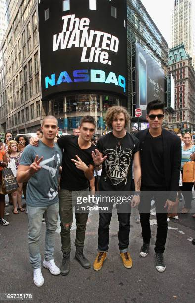 Singers Max George Tom Parker Jay McGuiness and Siva Kaneswaran of The Wanted ring the closing bell at the NASDAQ MarketSite on May 31 2013 in New...