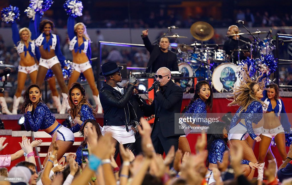 Singers Ne-Yo and Pitbull perform during halftime of the Thanksgiving Day game between the Philadelphia Eagles and the Dallas Cowboys at AT&T Stadium on November 27, 2014 in Arlington, Texas.