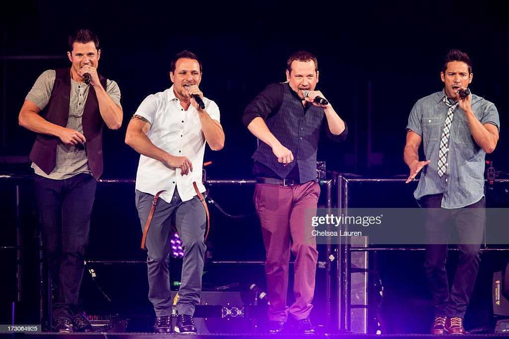Singers Nick Lachey Drew Lachey Justin Jeffre and Jeff Timmons of 98 Degrees perform at Staples Center on July 5 2013 in Los Angeles California