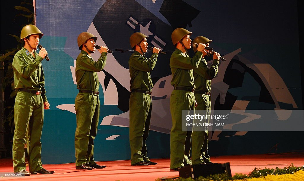 Singers perform at the venue marking the 40th anniversary of 'Dien Bien Phu in the air' or victory over US Airforce B-52's Christmas bombing, in Hanoi on December 29, 2012. Hanoi claimed downing some 34 US B-52 aircrafts during the 12-day US bombing campaign in December 1972 over Hanoi and neighbouring provinces. The meeting is the final event of a month-long celebration organised by the government. AFP PHOTO/HOANG DINH Nam