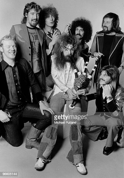 Singersongwriter and musician Roy Wood plays the bagpipes surrounded by the other members of English pop group Wizzard London December 1974