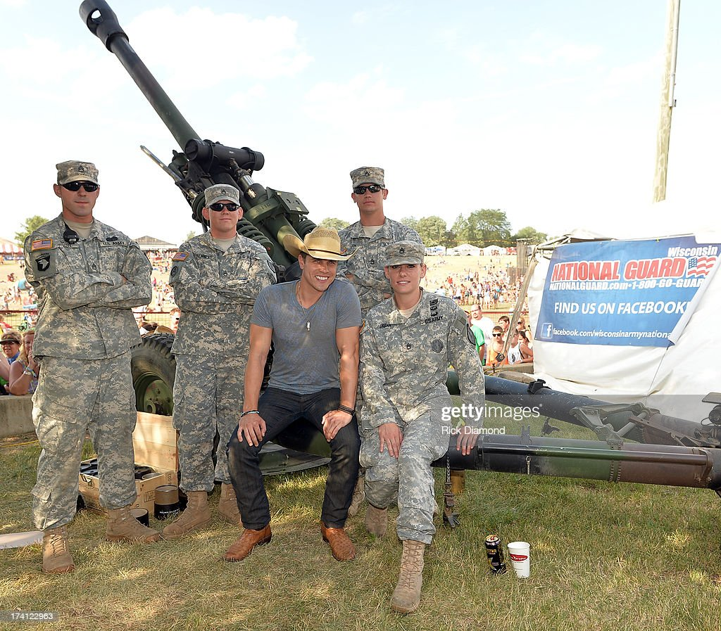 Singer/Songwriter <a gi-track='captionPersonalityLinkClicked' href=/galleries/search?phrase=Dustin+Lynch&family=editorial&specificpeople=8612719 ng-click='$event.stopPropagation()'>Dustin Lynch</a> poses by a Howitzer 105mm cannon with members of the Wisconsin National Guard at Country Thunder - Twin Lakes, Wisconsin - Day 2 on July 19, 2013 in Twin Lakes, Wisconsin.
