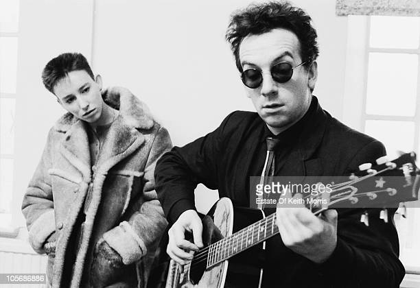 Singersongwriter Elvis Costello plays the guitar as his wife Cait O'Riordan looks on London 1986 O'Riordan was formerly the bassist with The Pogues