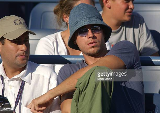 Singer/songwriter Enrique Iglesias watches his girlfriend Anna Kournikova play a doubles match at the US Open September 4 2002 in Flushing Meadows...