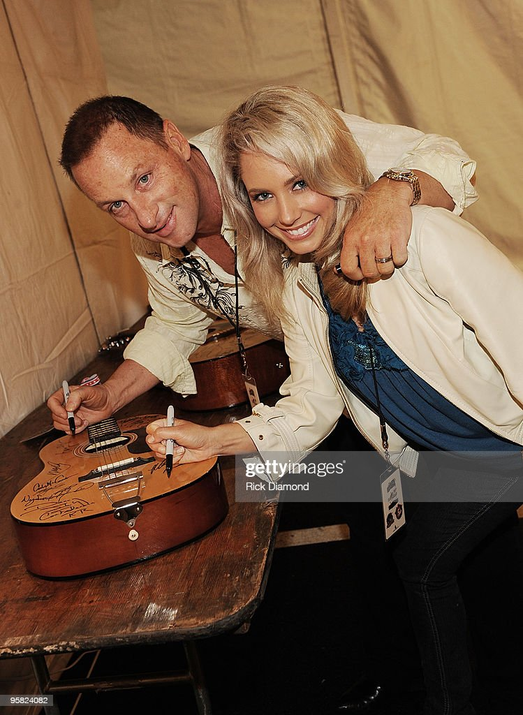 Singer/Songwriter Gary Chapman and his wife Cassie Chapman autograph a guitar for charity backstage during the Country Crossing Grand Opening Kick-Off Celebration at Country Crossing on January 16, 2010 in Dothan, Alabama.