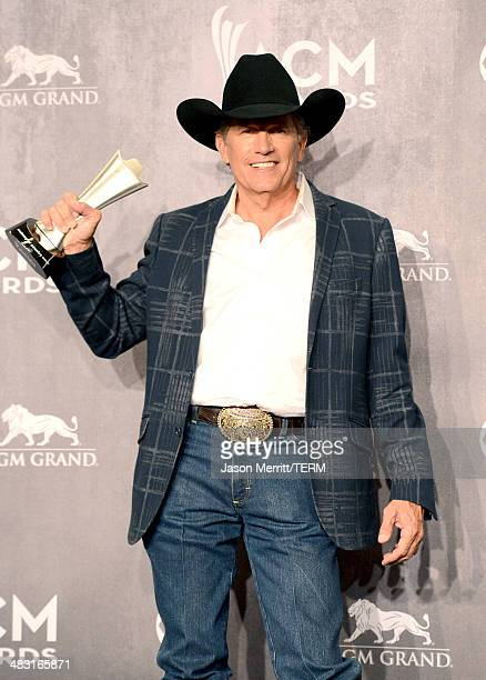 Singer/songwriter George Strait poses in the press room with the Entertainer of the Year award during the 49th Annual Academy of Country Music Awards...