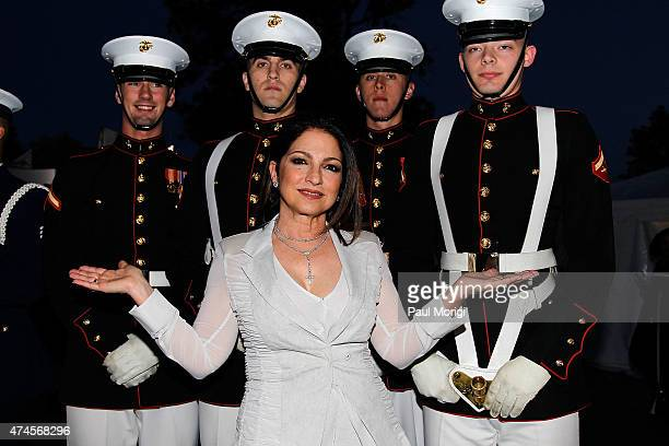 Singersongwriter Gloria Estefan poses for a photo with Marines at the 26th National Memorial Day Concert Rehearsals on May 23 2015 in Washington DC