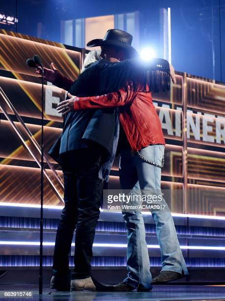 Singersongwriter Jason Aldean accepts the Entertainer of the Year award from muscian Joe Walsh onstage during the 52nd Academy of Country Music...