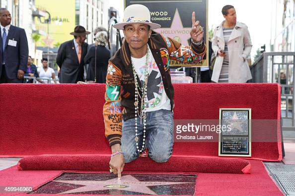 Singersongwriter Pharrell Williams attends the ceremony honoring him with a star on the Hollywood Walk of Fame on December 4 2014 in Hollywood...