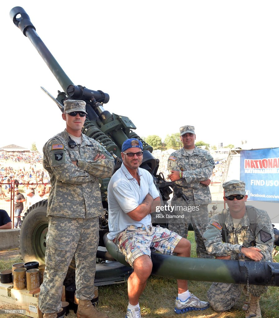 Singer/Songwriter <a gi-track='captionPersonalityLinkClicked' href=/galleries/search?phrase=Phil+Vassar&family=editorial&specificpeople=619225 ng-click='$event.stopPropagation()'>Phil Vassar</a> poses by a Howitzer105mm cannon with members of the Wisconsin National Guard Country Thunder - Twin Lakes, Wisconsin - Day 3 on July 20, 2013 in Twin Lakes, Wisconsin.