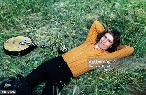 Singersongwriter Rino Gaetano lying on grass next to a chordophone musical instrument Italy 1978