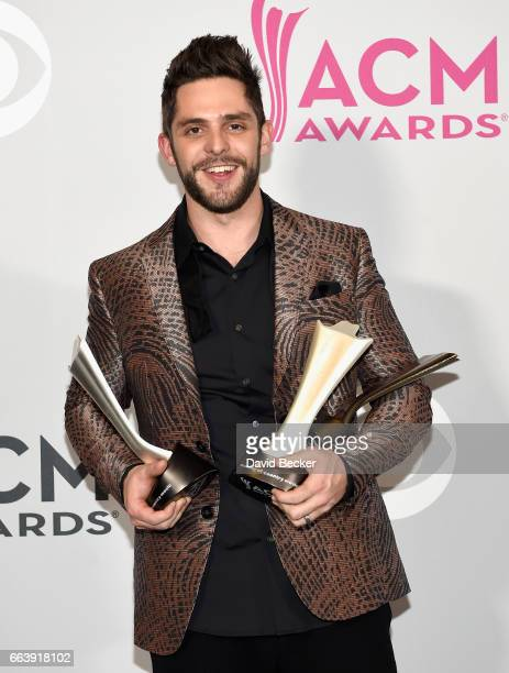 Singersongwriter Thomas Rhett winner of the awards for Male Vocalist of the Year and Song of the Year poses in the press room during the 52nd Academy...