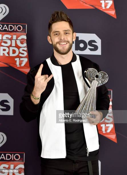 Singersongwriter Thomas Rhett winner of the Country Artist of the Year award poses in the press room at the 2017 iHeartRadio Music Awards which...