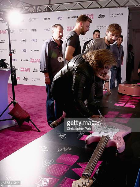 Singer/songwriters Hillary Scott Charles Kelley and Dave Haywood autograph a guitar during CBS Radio's We Can Survive at the Hollywood Bowl on...
