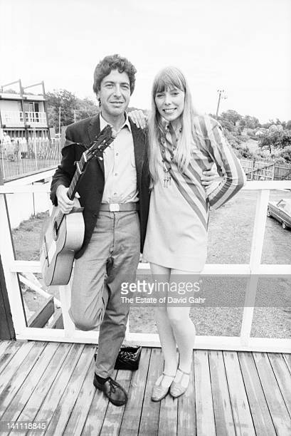 Singer/songwriters Leonard Cohen and Joni Mitchell meet backstage before separately performing at the Newport Folk Festival in July 1967 in Newport...