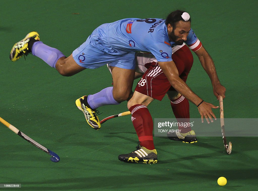 Singh Sardar of India (L) leaps over Mark Cleghorne of England (R) during their men's match at the International Super Series hockey tournament in Perth on November 22, 2012.