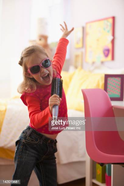 Singing Caucasian girl pretending hairbrush in microphone