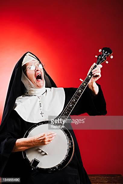 Singen ecstatically, die Nonne durch sich auf die banjo.