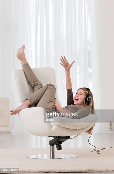 singing teenage girl in armchair with headphones