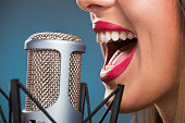 Close-up of female open mouth with red lipstick in front of microphone.