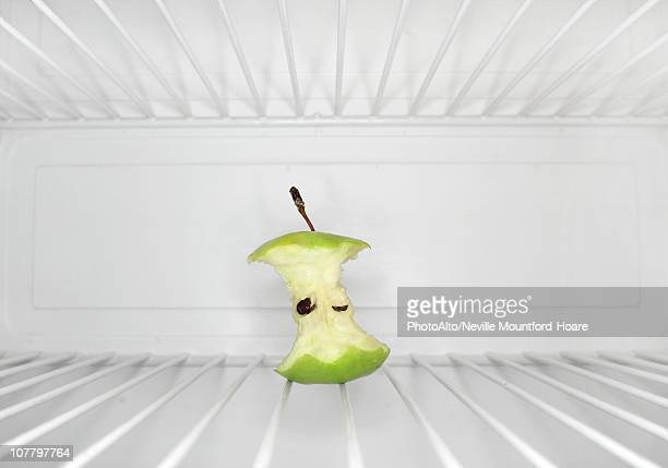 Single apple core sitting on shelf inside refrigerator