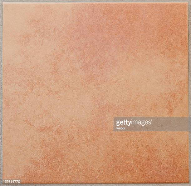 Single apricot colored ceramic tile textured full frame