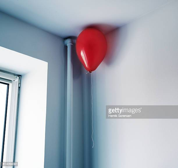 A single baalloon hanging in the corner of the ceiling.