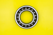 Single ball bearing close up, isolated on yellow background with copy space on the sides.