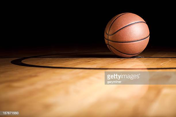 A single basketball sitting on the court