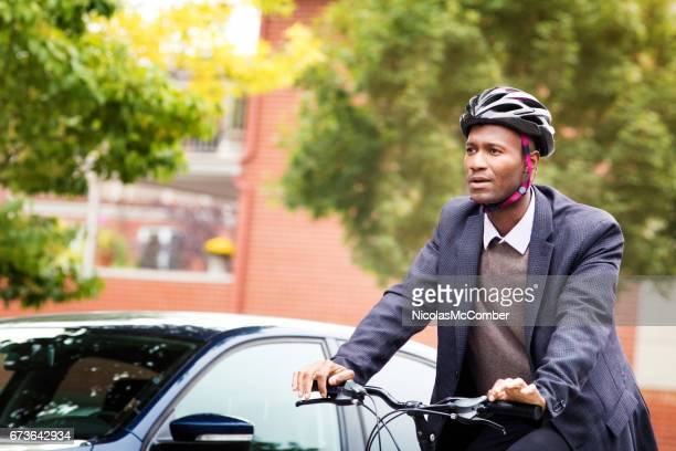 Single black male in his 30s cycling past car with helmet