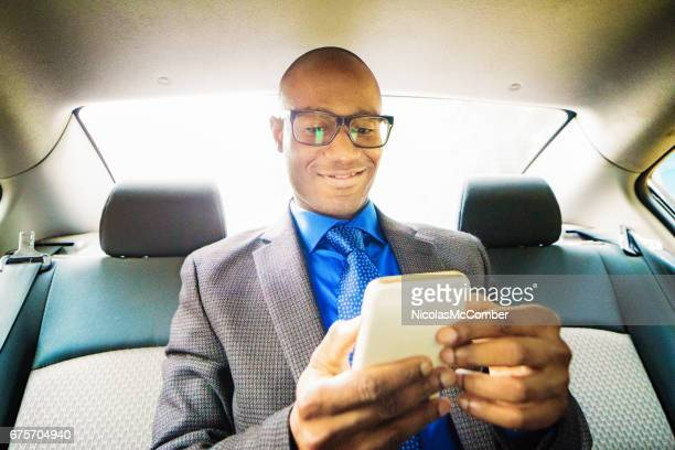 Single black male mid adult text messaging on mobile phone car back seat