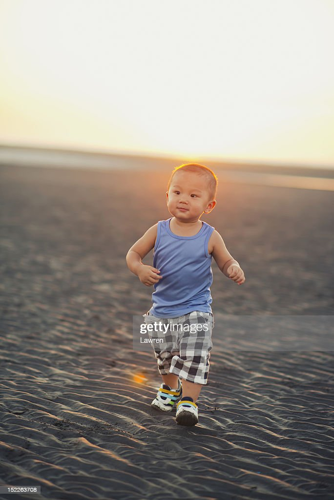 Single boy is walking on the beach : Stock Photo