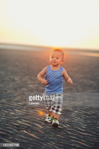 Single boy is walking on the beach : Stock Photo
