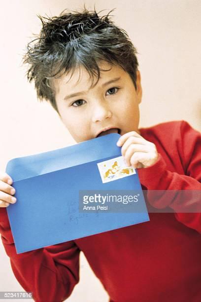 Single boy licking an envelope