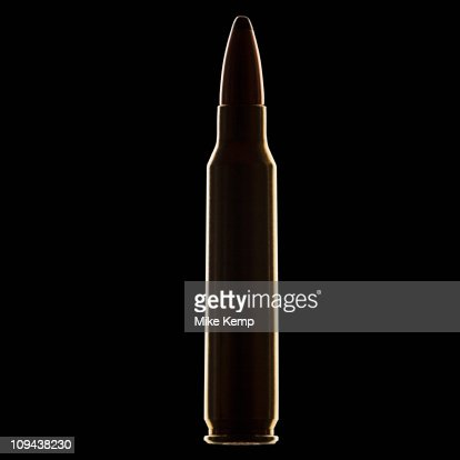 Single bullet on black background, close-up