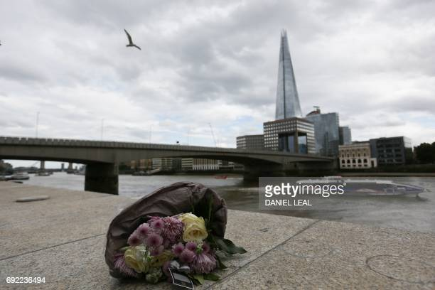 A single bunch of flowers lies on a wall on the northern bank of the River Thames close to London Bridge in London on June 4 in tribute to the...
