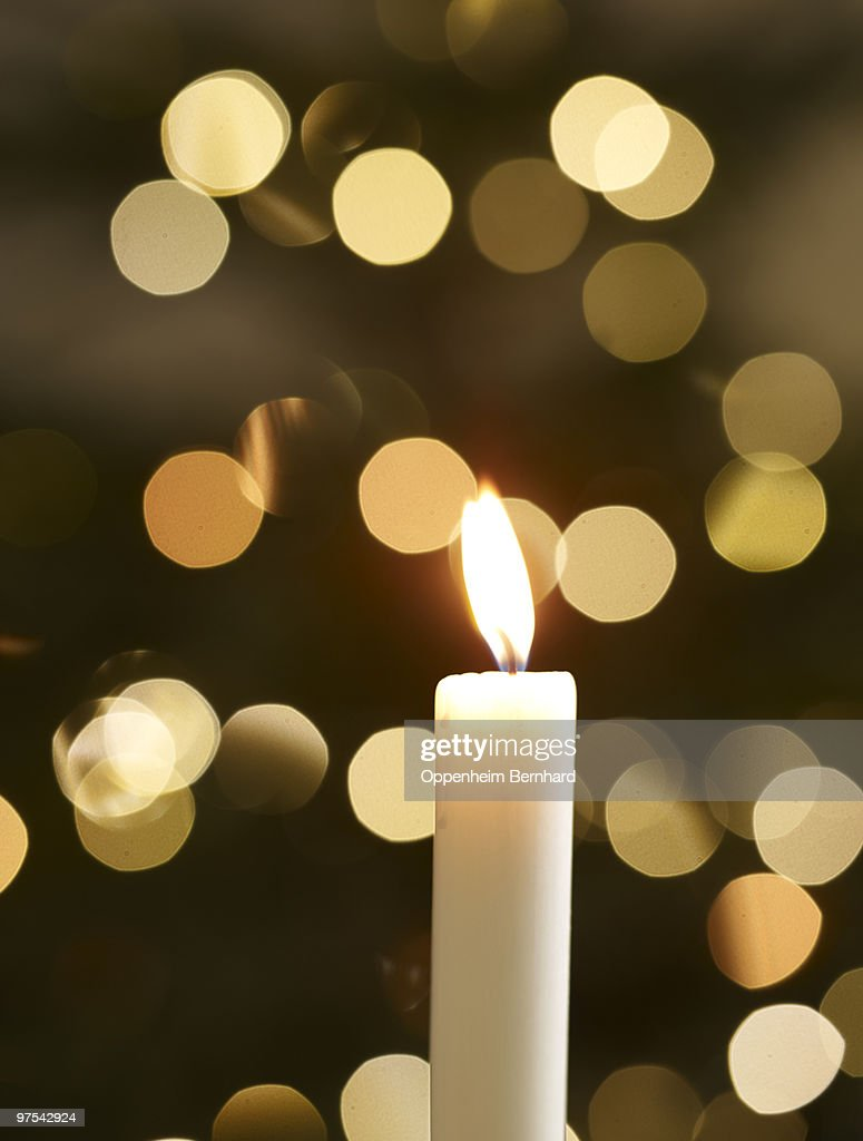 single candle with christmas lights in background : Stock Photo