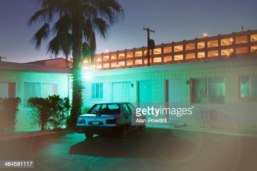 Single car at back of blue motel at night