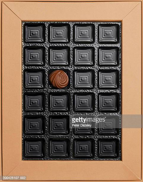 Single chocolate in empty box, overhead view
